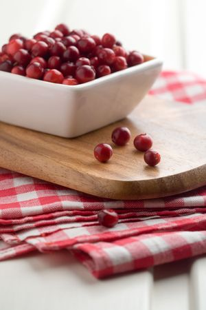 Fresh cranberries in white bowl, selective focus photo