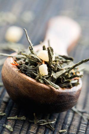 Fresh green tea leaves on wooden spun
