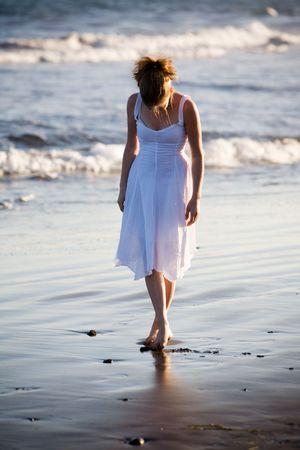 Woman walking on the beach photo