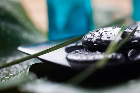 Black massage stones with water drops photo
