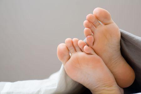 Dormir Teenager, les orteils montrant sous le drap
