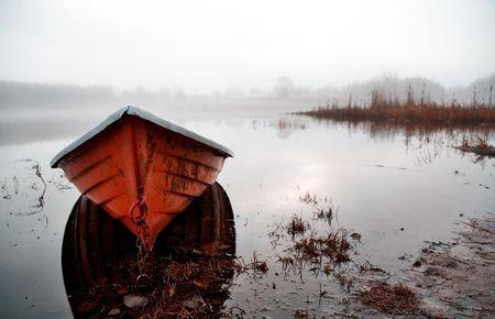 sunrise lake: Orange boat in beautiful morning misty light