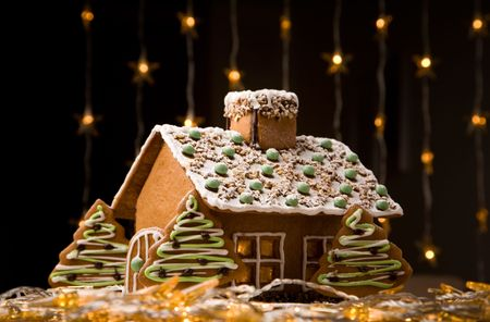 Beautiful gingerbread house with lights on dark background photo