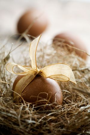 Brown easter egg with beautiful golden bow photo
