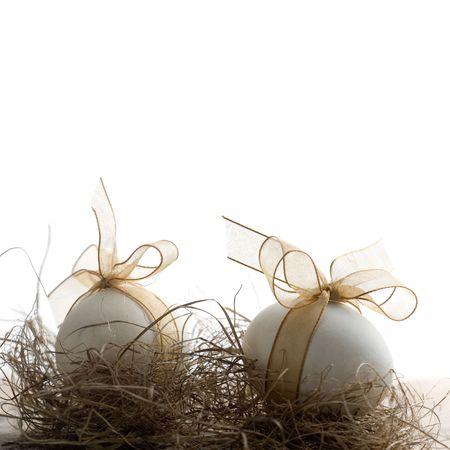 golden eggs: White easter eggs with beautiful golden bow Stock Photo