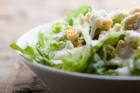 salad dressing: Ceasar salad with lots of dressing and parmesan  Stock Photo