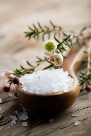 White bath salt on wooden spoon, shallow focus