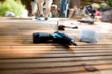 drill floor: Building a patio with wooden terrace and stones Stock Photo