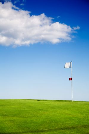 Putting green against blue sky with clouds photo