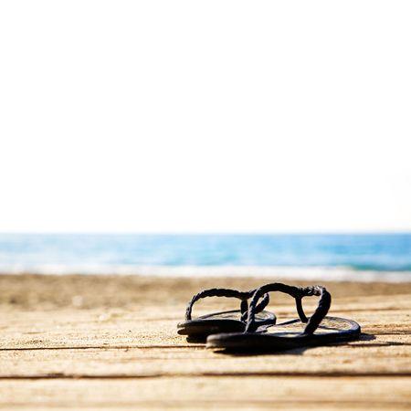 soleil rigolo: Sandales �t� noir sur le quai de sable  Banque d'images