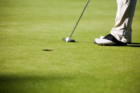 putt: Golfer putting, selective focus on golf ball Stock Photo