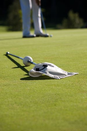 Golf green with white flag, shallow focus photo