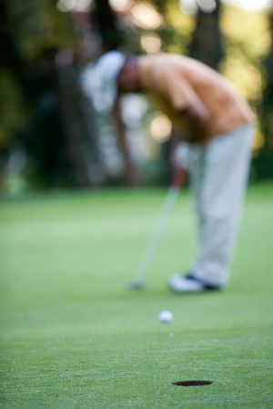 Golfer putting, selective focus on hole in front photo