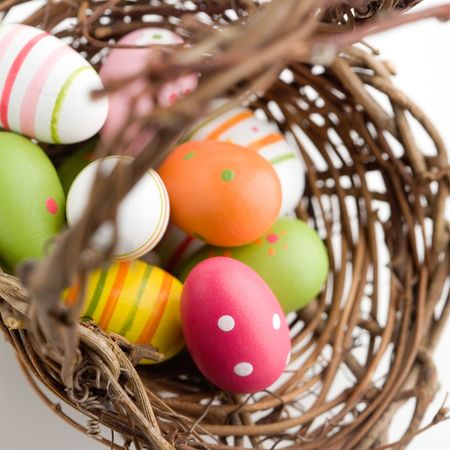 Colorful painted easter eggs in brown basket photo