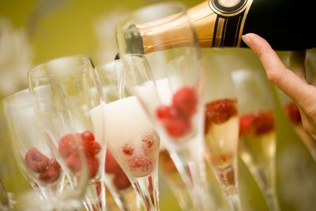 botella champagne: Champagne en gafas con frambuesas frescas de rojos  Foto de archivo