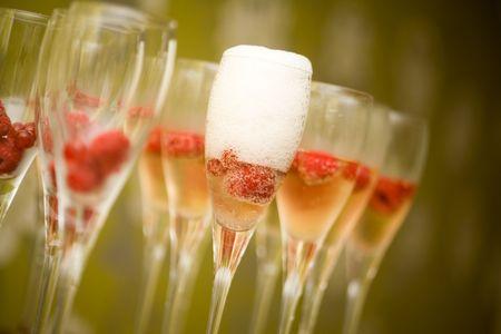 Champagne en gafas con frambuesas frescas de rojos  Foto de archivo