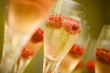 brindisi champagne: Champagne in bicchieri con lamponi freschi rossi