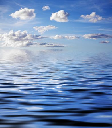 Blue sky with fluffy clouds and water reflection