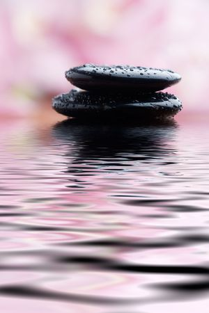 Black stones on water with pink background photo