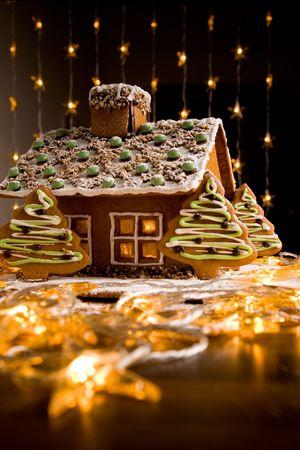 casita de dulces: Casa de pan de jengibre con luces dentro de fondo oscuro  Foto de archivo