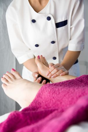 Young woman doing hot stone massage, shallow focus photo