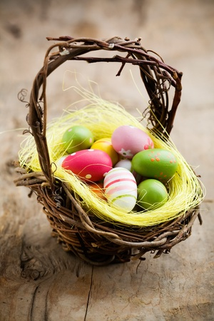 Colorful easter eggs in brown basket, shallow focus photo