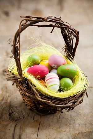 Kleurrijke Paas eieren in bruin mand, ondiepe focus Stockfoto