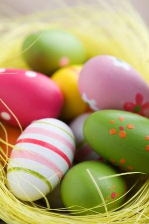Coloridos huevos de Pascua en cesta de marrón, enfoque de poco profunda