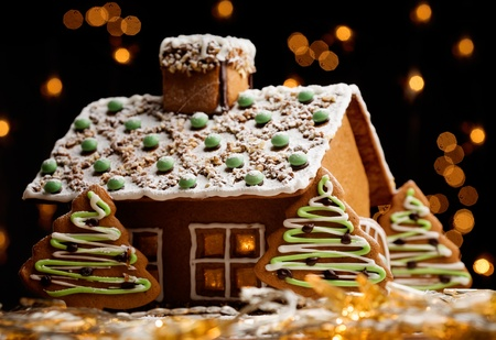 home baked: Gingerbread house with lights inside, dark background Stock Photo
