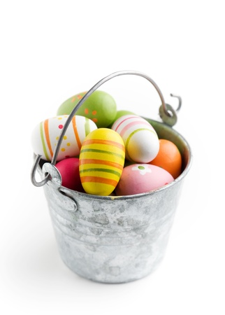 Colorful easter eggs in bucket, isolated on white photo