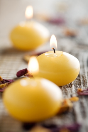 Close up of three yellow candles in row