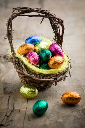 Colorful chocolate easter eggs in brown basket photo