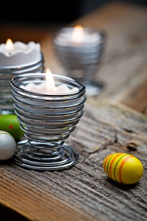 easter candle is burning: Easter candles on wooden table with egg decorations