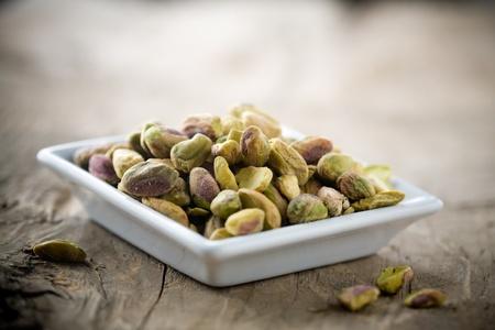 frutas deshidratadas: Peque�o recipiente de pistachos en mesa de madera