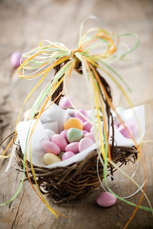 Colorful easter candy in brown basket with ribbon