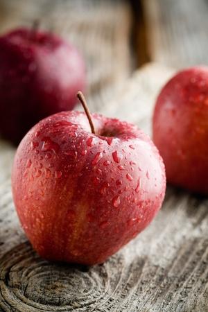 セレクティブ フォーカス木製テーブルの上の 3 つの赤いりんご 写真素材