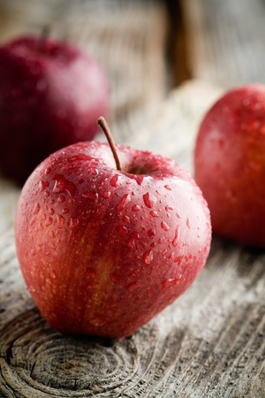 manzana roja: Tres manzanas rojas en mesa de madera, enfoque selectivo