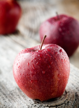 Three red apples on wooden table, selective focus photo
