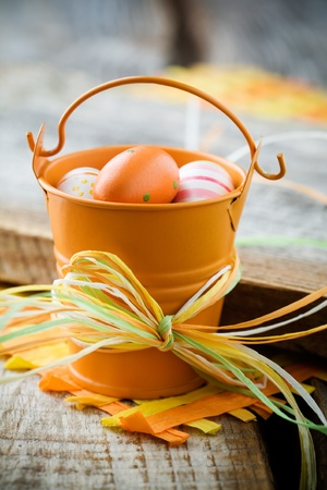 Colourful easter eggs in orange bucket, selective focus photo