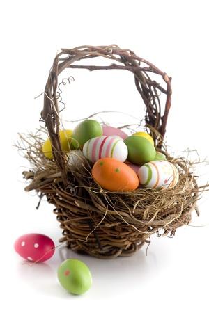 giftbasket: Kleurrijke Pasen eieren op groen gras, geïsoleerd op wit Stockfoto