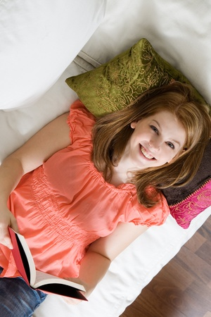 Young attractive woman reading a book on sofa photo