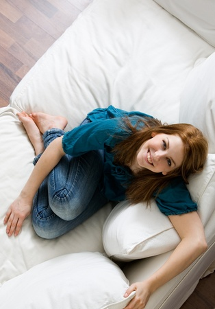 Young attractive woman relaxing on white sofa Stock Photo - 9042892