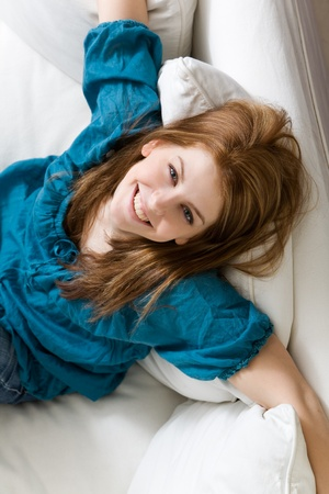 Young attractive woman relaxing on white sofa photo