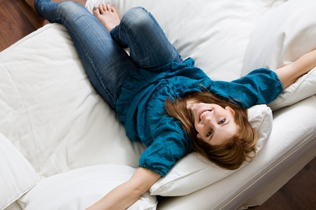 Young attractive woman relaxing on white sofa