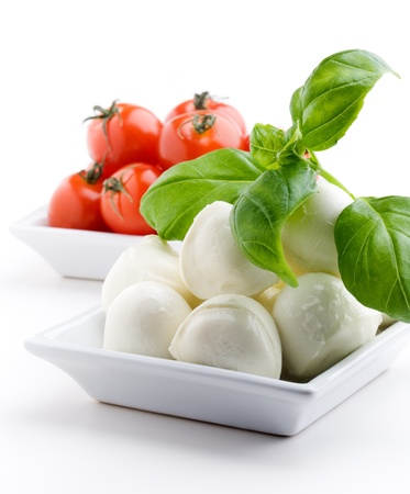 Mozzarella, tomaten en verse basilicum bladeren op witte achtergrond Stockfoto