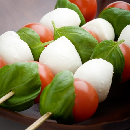 toothpick: Mozzarella, tomatoes and fresh basil leaves on white background