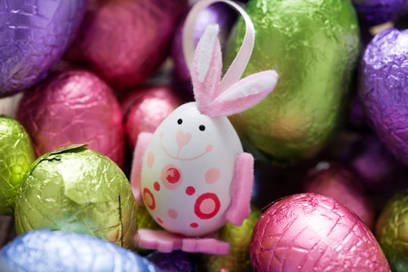 Easter bunny in the middle of chocolate eggs, selective focus photo