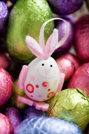 middle easter: Easter bunny in the middle of chocolate eggs, selective focus Stock Photo