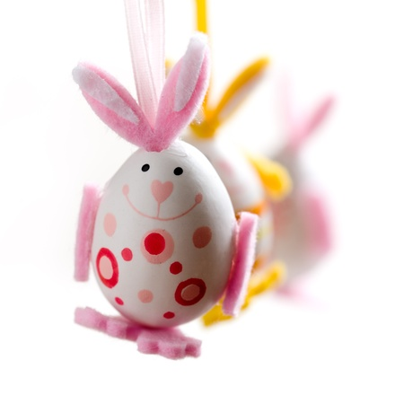 Easter bunnies hanging on white background, selective focus photo