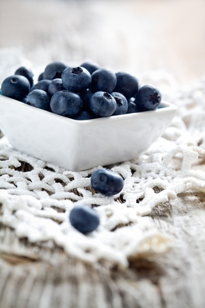 Fresh blueberries on wooden table, selective focus photo